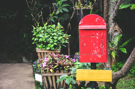 old red wooden mailbox on black pillar with blank yellow wooden sign in the garden background, copy space, vintage effect