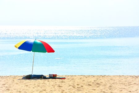 colorful beach umbrella with a cushion and small pillow on deserted beach in a sunny day, Phuket, Thailand