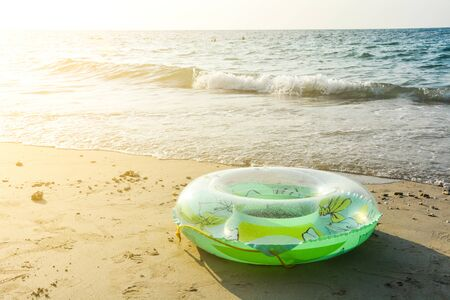 green inflatable round tube, plastic swim ring on the sand beach with sunlight in the evening Stok Fotoğraf
