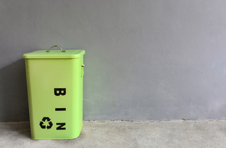 green metal recycle bin on grey cement background, copy space