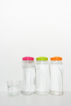 plastic bottles of drinking water and glass on white background, copy space