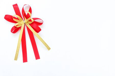 red and gold satin bow ribbon at the corner on white background