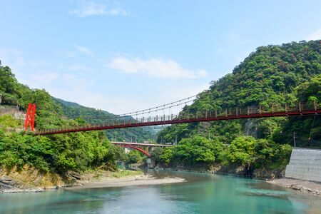 red hanging bridge or suspension bridge above the green river in the valley, Wulai, Taiwan
