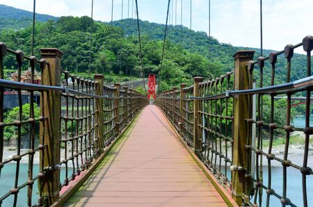 the walkway on red hanging bridge or suspension bridge above the green river in the valley, Wulai, Taiwan