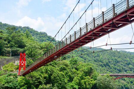 red hanging bridge or suspension bridge in the valley, Wulai, Taiwan
