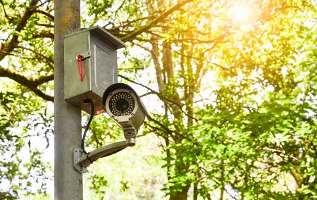 old white CCTV camera or surveillance on the pole for monitoring in public park
