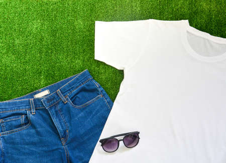 outfit of casual man, top view of white t-shirt and blue jeans with sunglasses on green artificial grass background, copy space