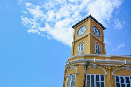 yellow building with clock tower in Chino-Portuguese style on blue sky background, Phuket old town, Thailand, copy space