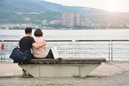 back view of loving couple hugging and sitting on bench at the seaside with sunset view background