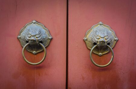 old Chinese lion doorknob on brown wood background Stok Fotoğraf