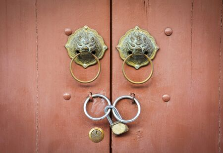old Chinese lion doorknob and padlock on close brown wood door background Stok Fotoğraf