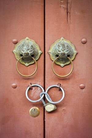old Chinese lion doorknob and padlock on close brown wood door background Stock Photo
