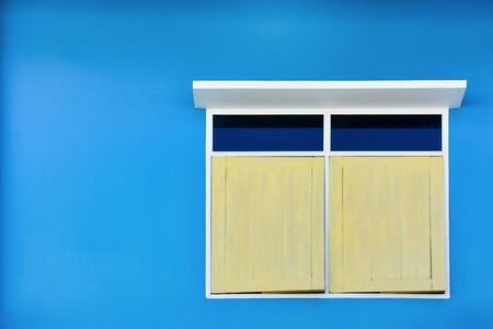 yellow simple vintage window with white awning isolated on blue cement wall background, copy space