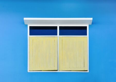 yellow simple vintage window with white awning isolated on blue cement wall background Stok Fotoğraf