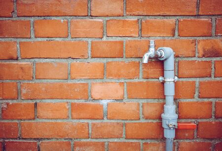 outdoor faucet water tap with gray PVC pipe and red valve   on red brick wall background texture, copy space, water saving concept