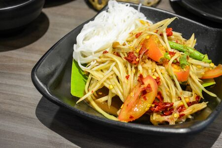 famous and popular Thai street food, green papaya spicy salad with pickled fish or Som Tum served with Thai rice noodles in black plate on wooden table background Stok Fotoğraf