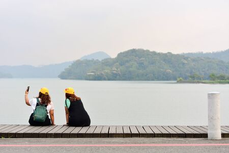 two young chubby woman taking selfie photos with a smartphone in the evening, sun-moon lake, Taiwan