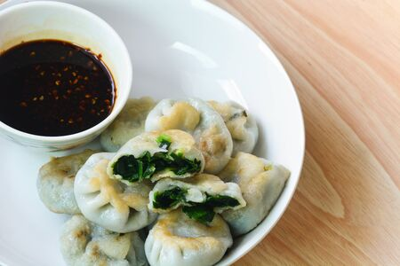 fried garlic chives dim sum or garlic steamed chives dumplings with spicy soy sauce in white plate on wood background