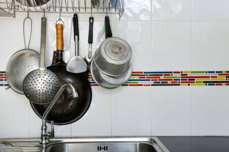old kitchenware hang on the white tile wall background