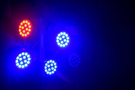 modern stage illumination equipment, red and blue beam of stage LED spot light on black background, copy space