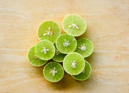 stack of cutting fresh lemon lime fruits on wooden chopping board background