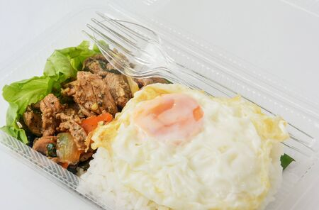 jasmine rice with spicy pork fried with Thai pepper and fried egg in a transparent plastic box package, ready to eat Stok Fotoğraf