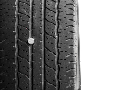 close up of rubber tires leak, automobile tire drilled with a metal screw nail, isolated on white background, copy space