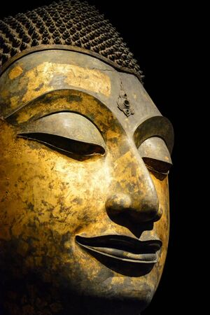 clipping path, close up of antique bronze Buddha face isolated on black background, copy space (selective focus)
