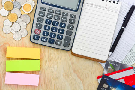 top view of credit cards, passbooks saving account, calculator, notebook with pen, pile of coins and colorful post-it notes on wood background, copy space, personal financial planning concept