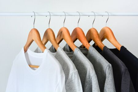 close up collection of black, gray and white color (monochrome) hanging on wooden clothes hanger in closet or clothing rack over white background