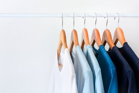close up collection shade of blue tone color t-shirts hanging on wooden clothes hanger in closet or clothing rack over white background with copy space Stock fotó