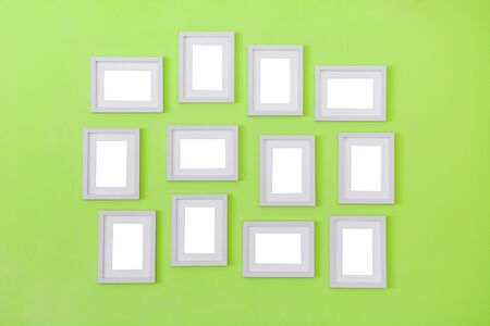 many of simple white blank small picture frames hanging on green color wall background, copy space Reklamní fotografie