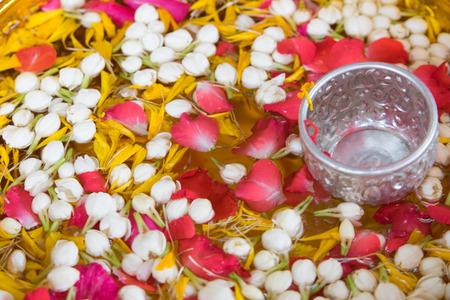songkarn 축제에서 작은은 사발과 함께 그릇에 재스민과 장미 화관과 물
