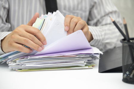 Man using hand looking for document on desk