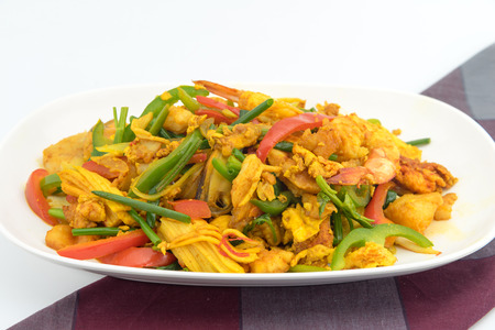 Seafood with Yellow curry sauce, sauteed seafood contains fish, shrimp, mussels, squid, crab claw, yellow curry powder, fresh garlic, egg, bell pepper, white onions, green onions celery photo