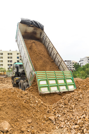 dumping: Dump truck dumps its load of rock and soil on land thailand Stock Photo
