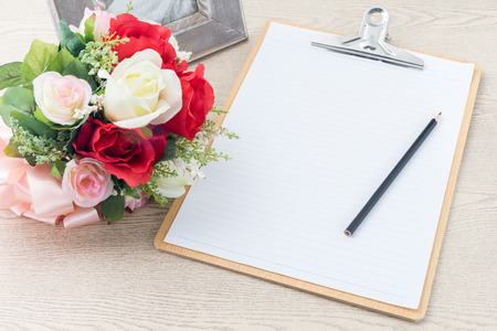 Wooden Clipboard attach planning paper with pencil on top beside rose bouquet on table