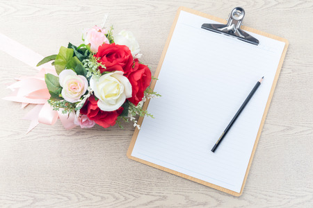 item list: Wooden Clipboard attach planning paper with pencil on top beside rose bouquet on table