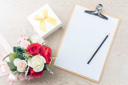 to attach: Wooden Clipboard attach planning paper with pencil on top beside rose bouquet  ,gift box on table