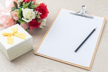 木製クリップボードはバラの花束、テーブルの上のギフト ボックスの横にある上に鉛筆で計画用紙を添付します。