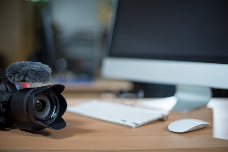 Video editing workstation with video camera beside monitor
