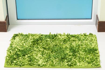 toilet door: Green cleaning feet doormat or carpet in front of toilet door look dirty Stock Photo
