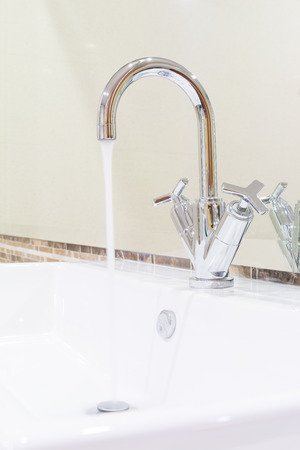 white sink washbasin and silver curve design faucet in modern design bathroom