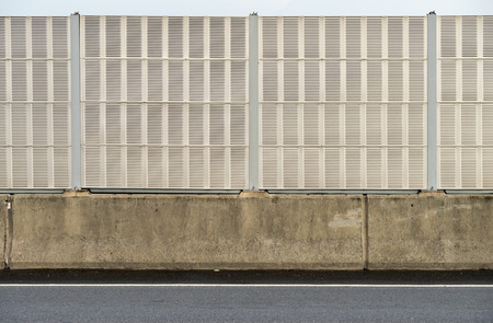 Noise barrier wall beside the highway to protect resident from noise photo