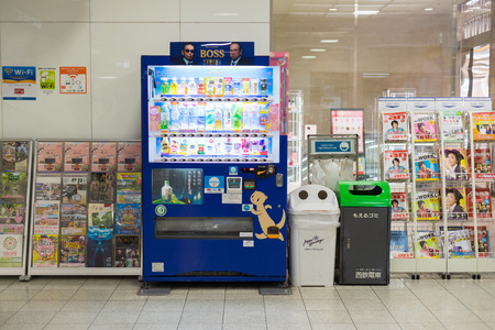 shelf ice: Fukuoka, Japan - October 14, 2014: The automatic vending machine in train station with recycle trash and magazine stand beside Editorial