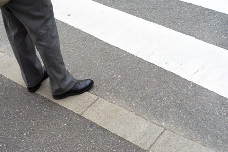 slag: Man legs in slag pants with shoes waiting to cross the street at a crosswalk Stock Photo