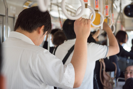 Many men taking ride in the bus hand holding onto a handle on a bus