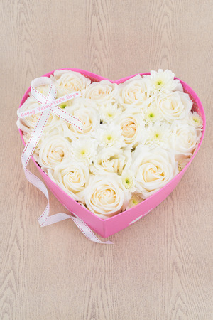 diamond shape: White roses and pearl and diamond held in the heart shape box with happy valentines day text label. gift for valentine s day on wooden background