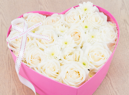 White roses and pearl and diamond held in the heart shape box with happy valentines day text label. gift for valentine s day on wooden background photo