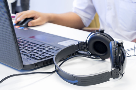 audio: Man hand using keyboard and mouse to control laptop with headphone beside working in music editing studio production